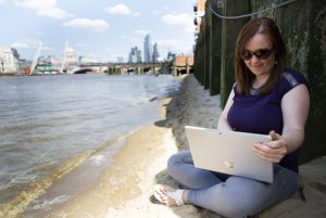 Manuela-working-remotely-in-London-by-Thames-writing